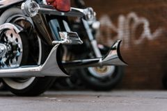 Shiny chromed retro fishtail exhausted pipes of luxury motorcycle. Brick wall with defocused graffiti in background. Soft lighting, vintage look Stock Photography