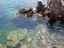 Shiny and clean sea at Menorca. A nice corner near a beach, surrounded by fantastic stones, clean sea and amazing day royalty free stock image