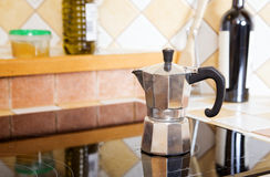 Shiny coffee pot at stove and liquid Royalty Free Stock Photo
