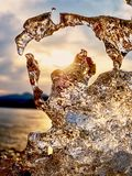 Shiny cold ice, bright icicles on frozen lake shore. Warm sun rays of sunset.  Reflection Royalty Free Stock Photography