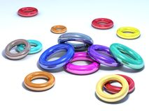 Shiny colored rings. It's a conceptual picture, some multicolored shiny rings on a white floor stock illustration