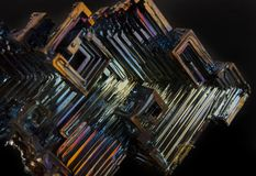 Shiny colorful mineral bismuth on a dark background. Rainbow shiny colorful mineral bismuth closeup macro on a dark background Royalty Free Stock Photography