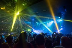 Shiny confetti during concert and crowd. Of spectators with their hands up Stock Photos