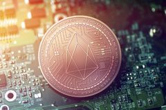 Shiny copper EOS cryptocurrency coin on blurry motherboard background. Token Stock Images