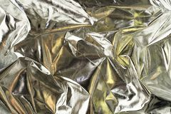 Shiny crumpled surface of silver foil with gold reflects for textured background. Textured silver foil background with shiny crumpled surface and gold reflects royalty free stock image