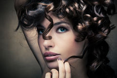 Shiny curly hair. Sensual brunette woman with shiny curly silky hair studio shot royalty free stock photos