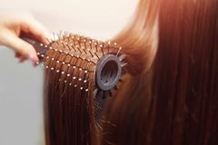 Shiny dark brown hair lying on round brush in hand of female. Care master beauty salon royalty free stock photos