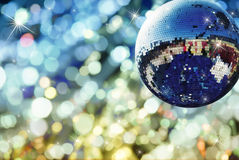 Shiny disco ball. With colored light background Royalty Free Stock Image