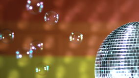 Shiny disco ball spinning with floating bubbles against rainbow flag stock footage