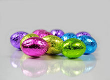 Shiny Foil Chocolate Eggs Reflected. Bright shiny foil candy Easter eggs with a light reflection on a pale gray background stock image