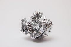 Shiny foil, crumpled into a ball on a white background. Shiny foil color steel, crumpled into a ball on a white background Royalty Free Stock Images