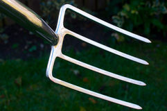 Shiny Garden Fork. With garden in the background Royalty Free Stock Photo
