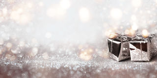 Shiny gifts on a silver bokeh background. Shiny gifts on a silver sparkling bokeh background for a festive concept stock image