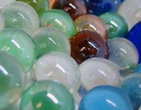 Shiny glass marbles background. A pile of shiny glass marbles of different colours: green, brown, blue, cyan, white Royalty Free Stock Image