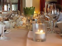 Shiny glasses and service on a dinner table at a restaurant. Dinner table full of shiny glasses and service decorated with candles and flowers at a restaurant Stock Photo