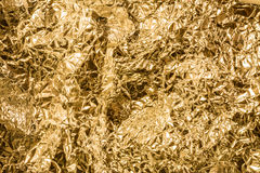 Shiny gold abstract background. Vivid gleamy texture from crumpled tinfoil. Concept of luxury or gilt royalty free stock images