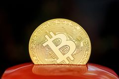 Shiny gold bitcoin sticking up from the red money box stock photo