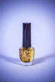 Shiny gold bottle female nail polish Royalty Free Stock Photo