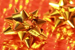Shiny gold of gift bow on gold. Metallic wrapping paper with reflected back-lighting Stock Photos
