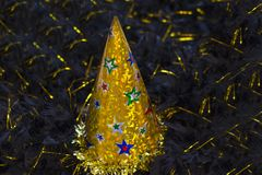Shiny gold party hat. On black background with sequins stock photo