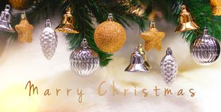 Shiny gold and silver christmas balls, stars and bells on white with pine tree for new year with marry christmas text.  stock photography