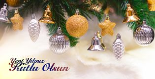 Shiny gold and silver christmas balls, stars and bells on white with pine tree. Yeni yiliniz kutlu olsun means happy new year stock image