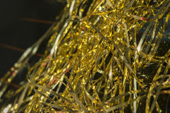 Shiny gold tinsel on black background shimmers in the sunlight. royalty free stock image