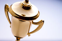 Shiny gold trophy award. Close up high angle view of a shiny gold trophy award to be awarded to the winner or champion in a competition, with copyspace to the royalty free stock image