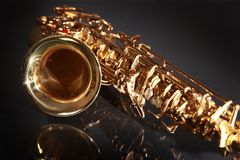 Shiny and golden. Shiny golden saxophone on black background Royalty Free Stock Images