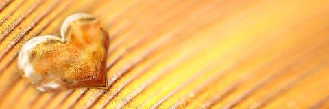 Shiny golden heart on gold background. Shiny golden heart on gold panoramic background stock photography