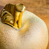 Shiny golden metallic apple on wooden background, Stock Photo