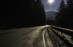 Shiny golden road in the Vosges mountains France-horizontal. A shiny golden road curve in the Vosges mountains France in winter with the sun in a blue sky Stock Photos