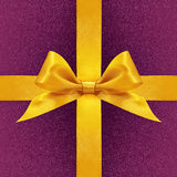 Shiny golden satin ribbon bow on purple Royalty Free Stock Photos