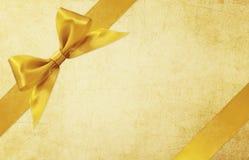 Shiny golden satin ribbon on gold background Stock Photography