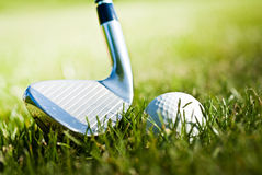 Shiny golf club and ball on the grass Royalty Free Stock Photography
