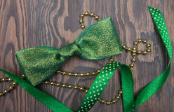 Shiny green bow tie, satin ribbon and gold beads on wooden table Stock Photos
