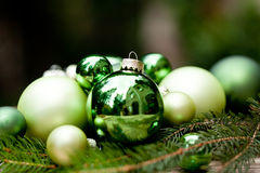 Shiny green christmas baubles closeup macro and tree Royalty Free Stock Images
