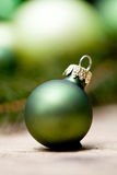 Shiny green christmas baubles closeup macro and tree Royalty Free Stock Photography