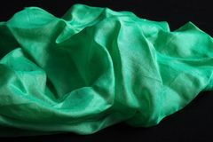 Shiny green silk handkerchief on black velvet Stock Photography