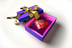 Shiny heart in a gift box, on a white surface. Stock Image