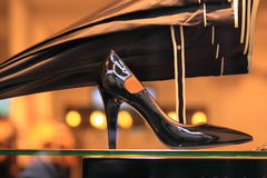 Shiny high heeled black pump Stock Images
