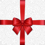 Shiny holiday red satin ribbon bow on white lacy ornamental  bac Royalty Free Stock Photos