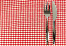 Shiny knife and fork. On a red and white checkered tablecloth Stock Photography