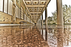 Shiny marble walkway. Beautiful architectural details of an outside covered walkway decorated in white and gold with stone pillars and a marble floor Stock Photography