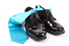 Shiny men's dressy shoes and blue tie Royalty Free Stock Photography