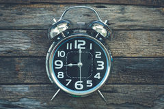 Shiny metal classic alarm clock on very old wooden table backgro Royalty Free Stock Photography