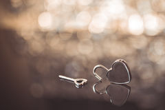 Shiny metal heart lock and key in brown light and bokeh background, old time theme, romantic and vintage look stock images
