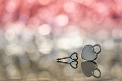 Shiny metal heart lock and key in red light and bokeh background Royalty Free Stock Images