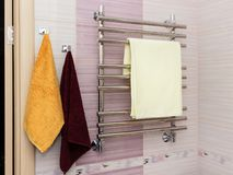 Shiny metal heated towel rail set in the bathroom dry towel. stock photography