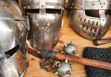 Shiny metal helmets of medieval knights with traditional weapons at a middle age theme festival. 